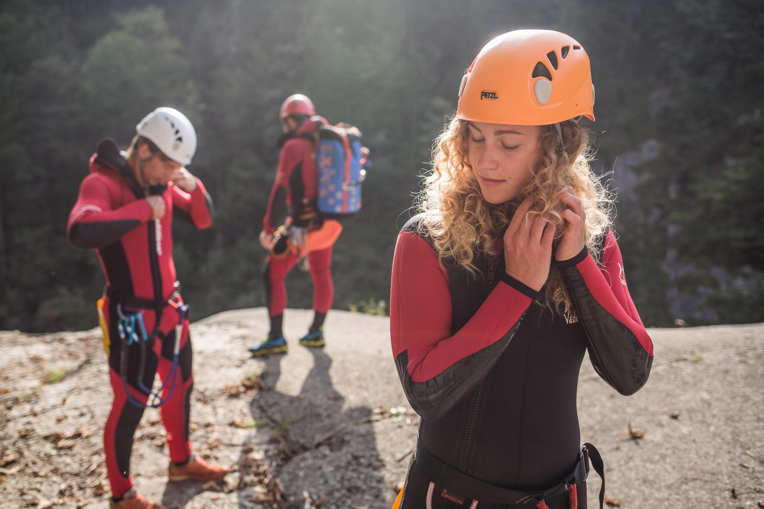 Eine junge Frau schließt Ihren Helm während der Canyoning-Guide in Salzburg wartet