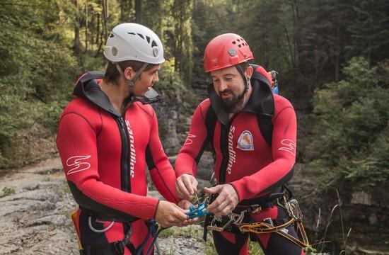 Beim Canyoning in der Almbachklamm gibt der Canyoning-Guide einem Mann die Einweisung bezüglich der Sicherung