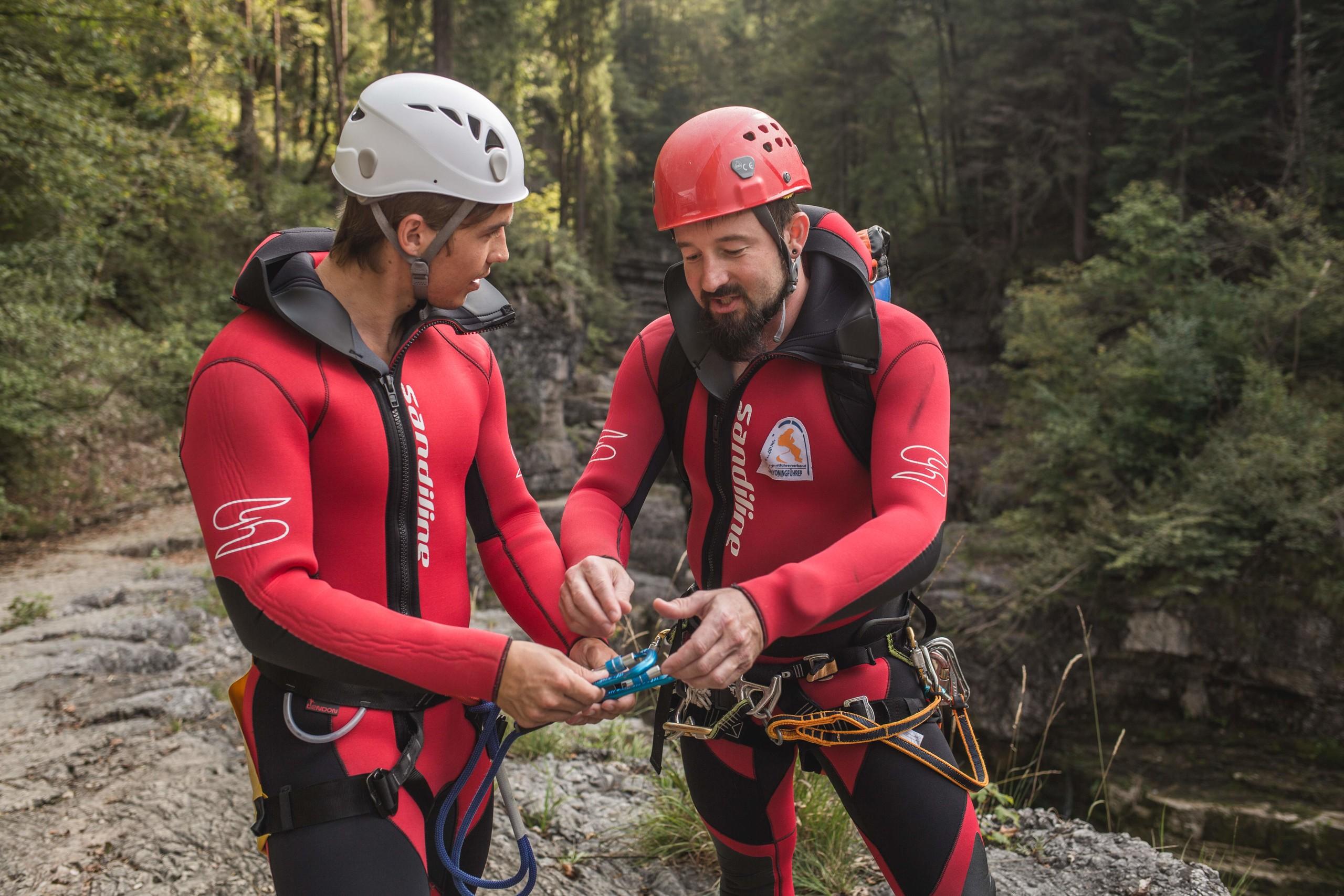 Der Canyoning-Guide Max Obermayr weist einen Mann bezüglich der Sicherung ein