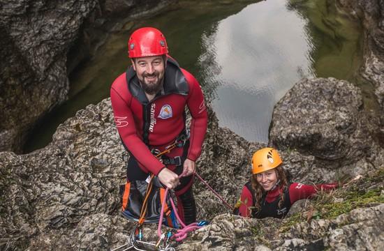 Der Canyoning-Guide in Salzburg lacht gemeinsam mit einer jungen Frau in die Kamera