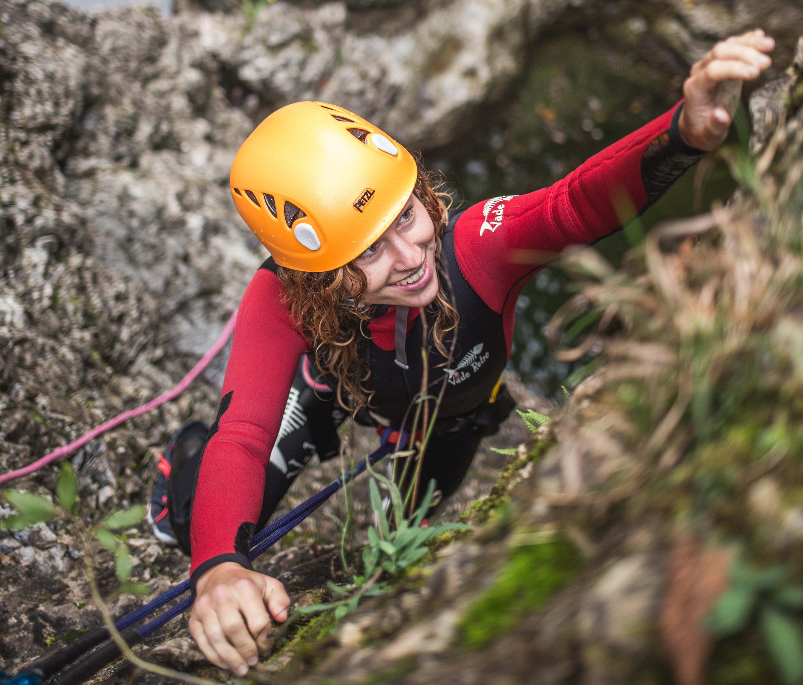 Eine junge Frau klettert beim Canyoning im Salzkammergut die Felswand hoch