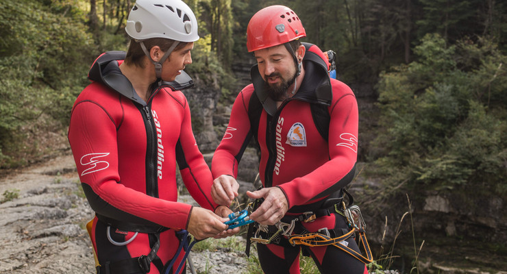 Der Canyoning-Guide in Salzburg weist einem Mann bezüglich der Sicherung ein