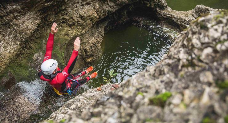 Ein Mann rutscht beim Canyoning in Salzburg auf den nassen Steinen ins Wasser