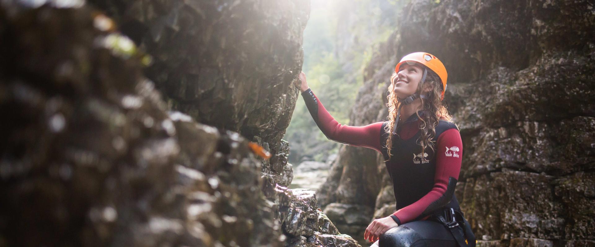 Beim Canyoning im Wiestal schaut eine junge Frau lächelnd die Felswand hinaus