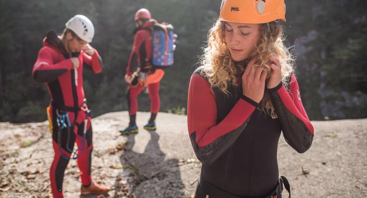 Beim Canyoning-Betriebsausflug schließt eine junge Frau ihren Helm