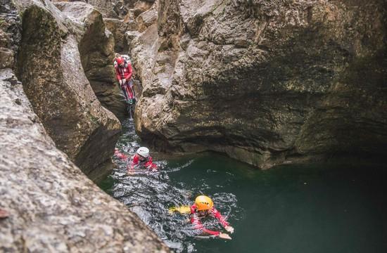Eine kleine Gruppe schwimmt beim Canyoning in der Almbachklamm durchs Wasser