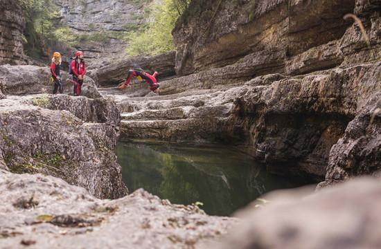 Beim Canyoning in der Almbachklamm springt ein Mann von einer Klippe ins Wasser