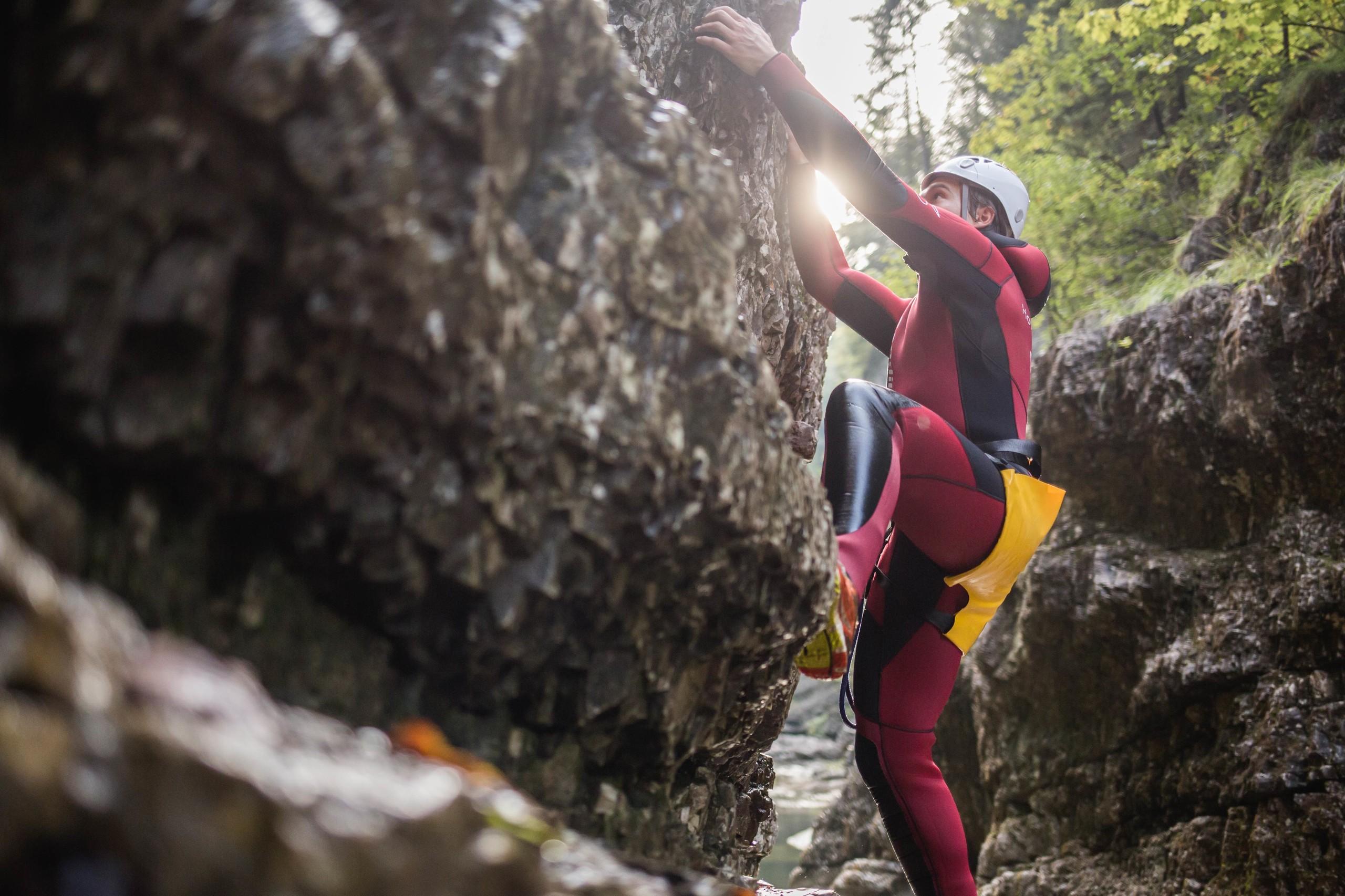 Ein Mann klettert beim Canyoning in der Strubklamm die Felswand hinauf