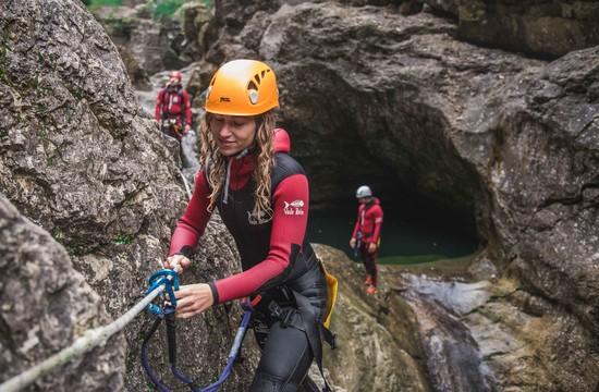 Eine junge Frau überprüft beim Canyoning in Salzburg die Sicherung