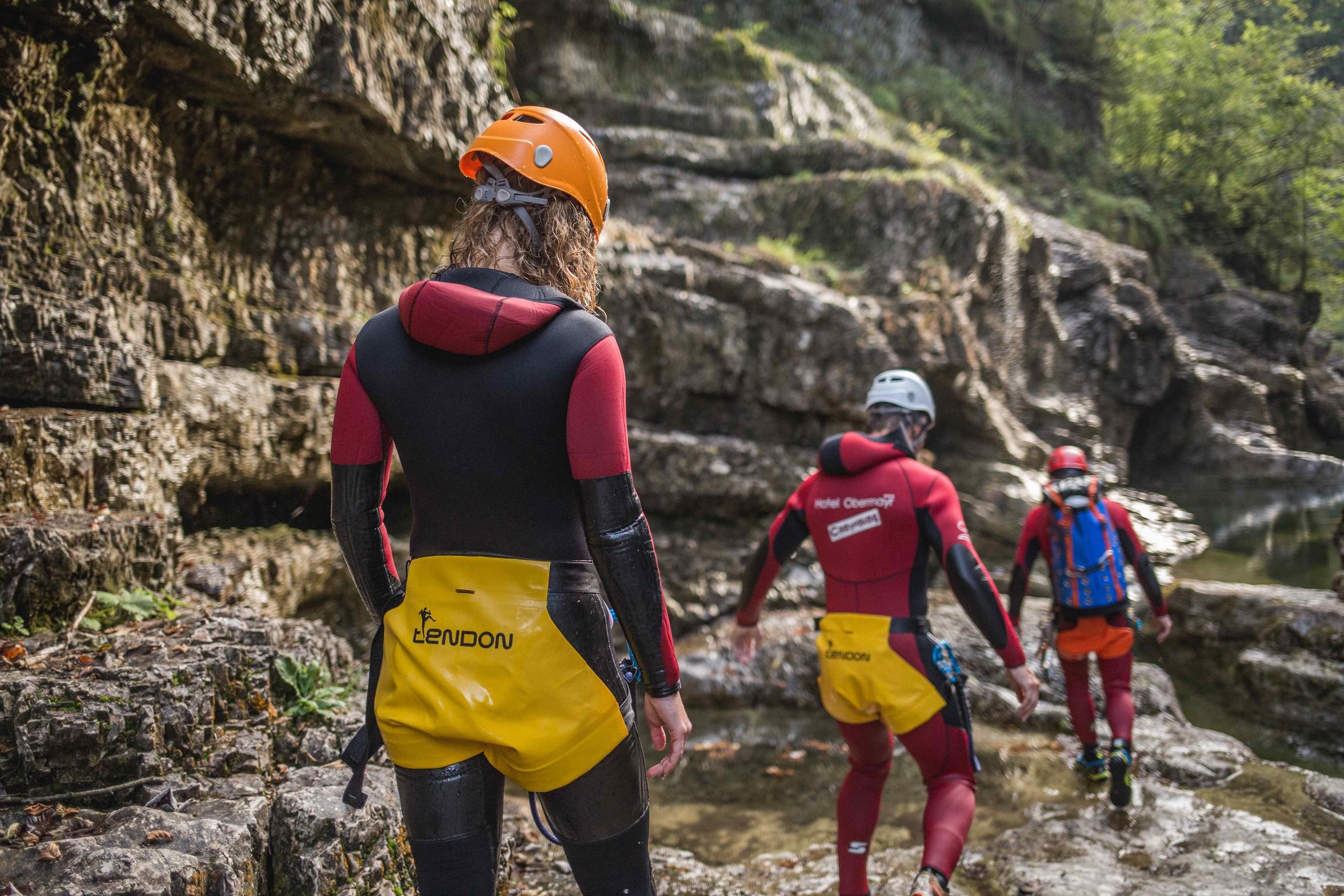 Beim Canyoning in der Almbachklamm steigt die Gruppe in der Ausrüstung über die nassen Felsen