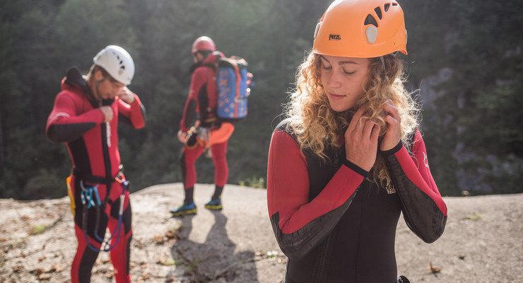 Beim Canyoning in der Almbachklamm schließt eine junge Frau ihren Helm