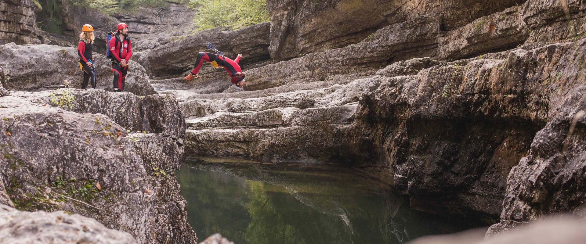Ein Mann springt beim Canyoning in Salzburg von einer Klippe ins Wasser