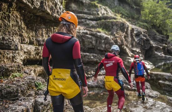 Beim Canyoning im Wiestal steigt eine kleine Gruppe über die nassen Felsen